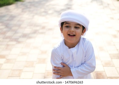 Portrait of Muslim boy on the streets wearing cultural kids wear in the Middle East Arab Countries called Kandura