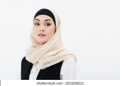 portrait of muslim businesswoman in hijab looking away isolated on grey