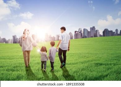 Porträt der muslimischen Familie, die bei einem Spaziergang auf der Wiese in Richtung der modernen Stadt Händchen hält