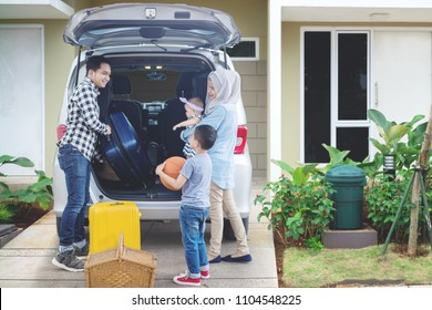 Portrait of Muslim family looks happy while preparing suitcase into a car for holiday. Shot in the house garage