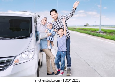 Portrait of Muslim family waving hands together at the camera while standing on the road near their car