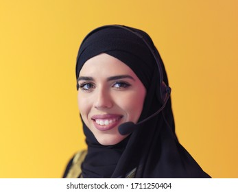 portrait of muslim female with hijab scarf customer representative business woman with phone headset helping and supporting online with customer in modern call centre isolated on yellow background