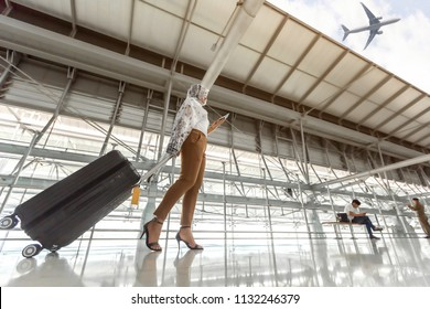 Portrait of a muslim immigrant woman wearing a hijab walking carrying a suitcase ,ticket and passport in hands going traveling by airplane at airport.