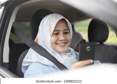 Portrait of muslim lady driver smiling happily when looking at her phone in the car, ride sharing concept