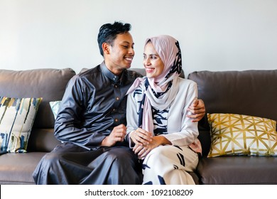 A portrait of a Muslim Malay couple at home during the Muslim festival of Hari Raya in Singapore, Asia. They are sitting on their home couch and smiling as they watch television.