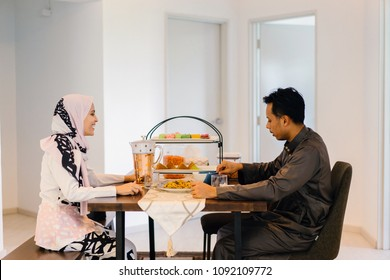 A portrait of a Muslim Malay couple at home during the Muslim festival of Hari Raya in Singapore, Asia. They are having a meal at home at their table.