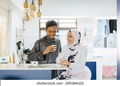 Portrait of a Muslim Malay couple in their home. They are having a moment as they break fast for Hari Raya.