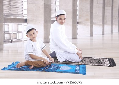 Portrait of Muslim man with his son wearing Islamic clothes while praying together in the mosque
