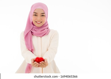 Portrait of Muslim woman in hijab holding red heart with beautiful smile, isolated white background with copy space