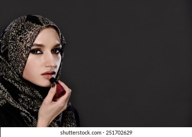 Portrait of Muslim woman painting her lips with a lipstick on gray background