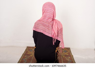 portrait of muslim woman praying alone sitting on a tablecloth, indoors
