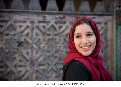 Portrait of muslim woman smiling in traditional clothing with red hijab and black dress in front of traditional arabesque decorated wall