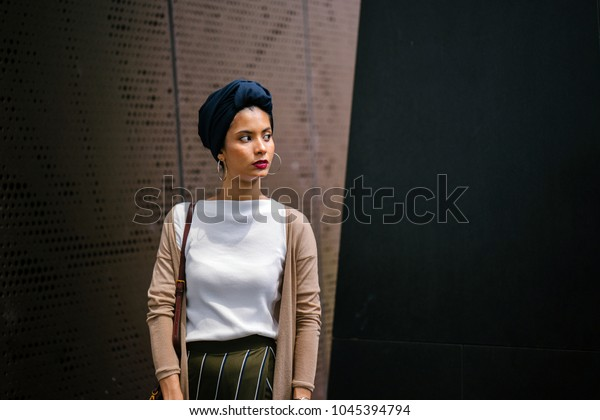 Portrait of a Muslim woman wearing a turban (hijab, head scarf) in a studio, against a metal background. She is elegantly dressed and Saudi Arabian, Malay, Asian descent.