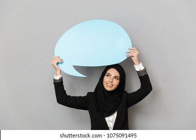 Portrait of muslim young woman 20s in black traditional clothing looking at camera while holding blue empty copyspace bubble for your text isolated over gray background