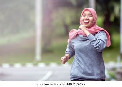 portrait of muslim young woman doing exercise and jogging outdoor at city park