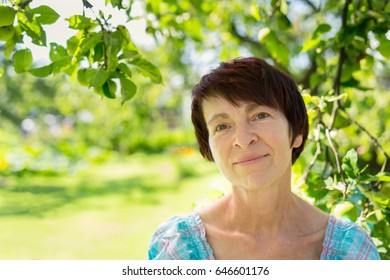 Portrait of a my mother - happy, middle aged woman in her garden