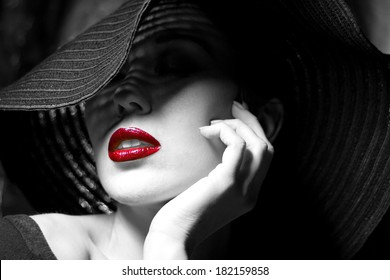 Portrait of mysterious beautiful young woman with wonderful skin texture  in  black hat. Trendy glamorous fashion makeup. Sensual red lips. Black and white image. Art photo