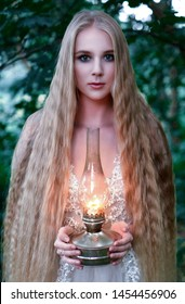 Portrait of a mysterious forest nymph with long blond hair and an oil lamp in her hands among green foliage