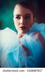 A portrait of a mysterious lady in a light blue dress posing indoor. Fairy tale, beauty, fashion.