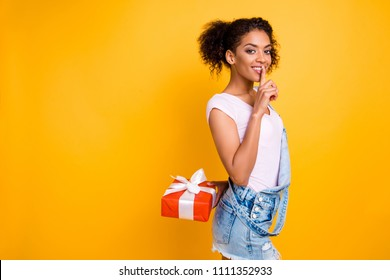 Portrait of mysterious pretty girl hiding gift case in red package with white bow behind back gesturing silence sign with forefinger making surprise isolated on yellow background with copy space