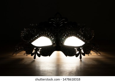 A portrait of a mysterious venetian mask with eyes of light shining through it. The darkness and mystery are perfect for a costumed ball or masquerade/halloween party.