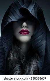 Portrait of mysterious woman in dark hood