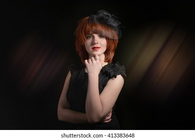 Portrait of the mysterious young and beautiful girl with fiery red hair and freckles in a black dress and hat veils