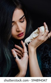 Portrait of a mysterious young girl holding a skull in the hands of a fox. Painted long hair jewelry rings on the fingers. Close-up. Closed eyes. Young witch before Halloween , bohemian.