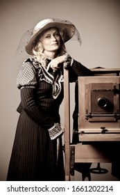 Portrait of a mysterious young positive woman with a modest long dress and hat posing near an old daguerreotype camera. Concept stylization of retro vintage photo.