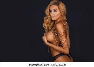 Portrait von nacktem schönen sexy blonden Mädchen mit langen Haaren und gegerbte Körper sinnliche posieren auf der schwarzen Wand.
