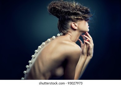 Portrait of naked beautiful woman on dark blue background