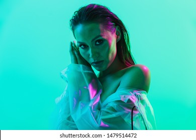 Portrait of naked gorgeous serious woman posing isolated over blue wall background with neon bright lights dressed in raincoat.