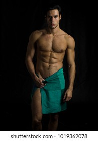 Portrait of naked handsome young man with languishing look covering crotch with a towel, against black background
