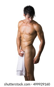 Portrait of naked handsome young man with languishing look covering crotch with a towel or a t-shirt, isolated on white background