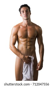 Portrait of naked handsome young man with languishing look covering crotch with a towel or a t-shirt