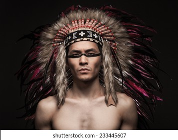 Portrait of the naked indian strong man posing with traditional native american make up  and headdress looking at the camera. Close up desaturated studio shot