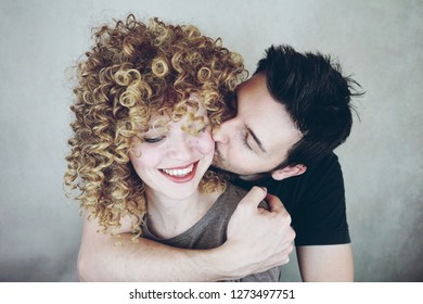 Portrait of a natural caucasian couple of young woman with curly blonde hair and man. He kisses her and she looks happy and smiles