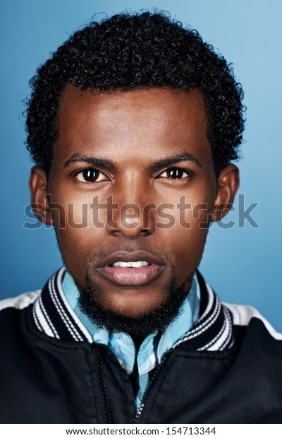 portrait of natural real african man on blue background