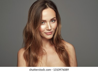 Portrait of natural sensual woman with long straight hair isolated over gray background