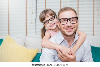 Portrait of nerd caucasian father daughter wearing glasses hugging and smiling. Nerdy daddy and little girl spending time at home . Fun love happy family lifestyle single dad love father's day concept