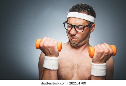 Portrait of a nerd guy trains with dumbbells. Topless funny man try to bodybuilding. Dark gray background. Studio shot