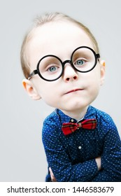 portrait of nerdy boy with big head and round glasses