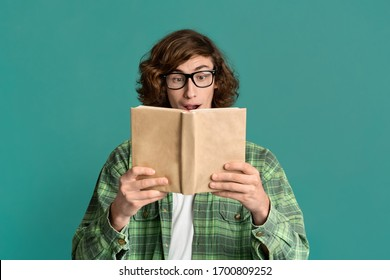 Portrait of nerdy young guy in glasses reading paper book on turquoise background