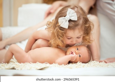 Portrait of a newborn baby with  being kissed by big sister