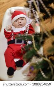 Portrait of newborn baby boy wearing Santa clothes under tthe Christmas tree