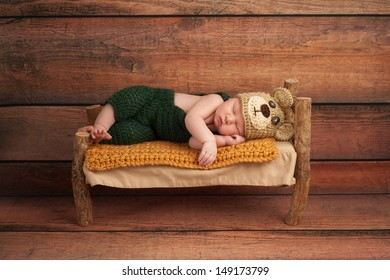 Portrait of a newborn baby boy wearing crocheted green overalls and bear hat. He is sleeping on a miniature wooden bed. Shot in the studio on a rustic wood background.
