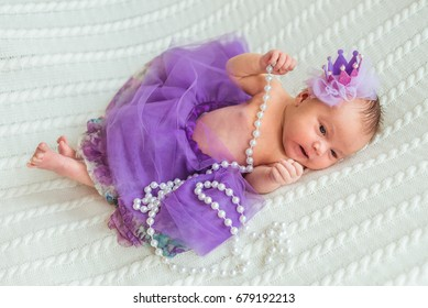 Portrait of newborn baby girl princess with crown sleeping on soft white blanket with imitation jewelry