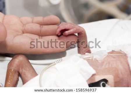 Portrait of newborn baby and hand inside incubator