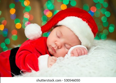 Portrait of newborn baby in Santa clothes lying under Christmas tree.
