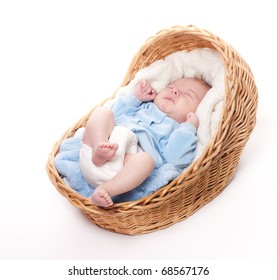 Portrait of newborn baby sleeping in basket with towel isolated over white background. Little baby sleeping alone and waiting for his parents: mother and father.